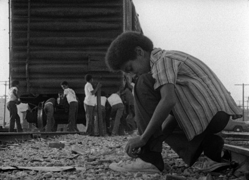 Kids playing by the train in the film KILLER OF SHEEP; a Milestone Film & Video release.