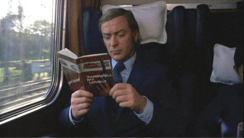 get-carter-1971-004-michael-caine-reading-chandler-in-train-seat